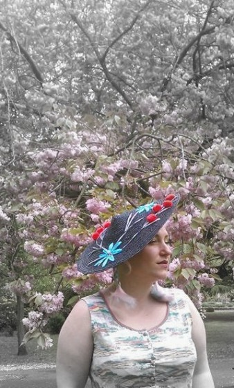 Straw coolie style hat with raffia embroidery. Model: Samantha Skouros